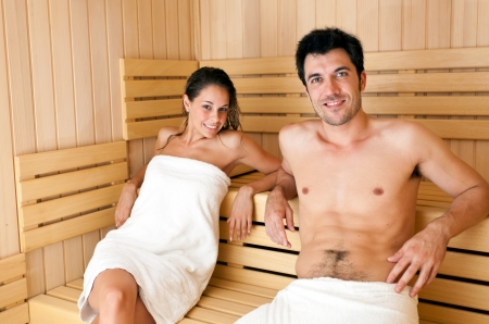Young beautiful woman having a sauna bath in a steam room photo