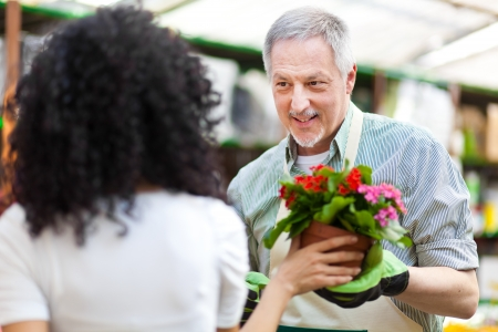 Portrait of a smiling greenhouse worker giving a flower pot to a customer Stock Photo - 19360201
