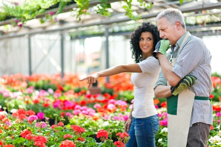 floriculture: Portrait of a greenhouse worker talking to a customer