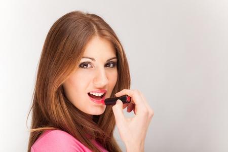 lip stick: Beautiful woman applying lipstick