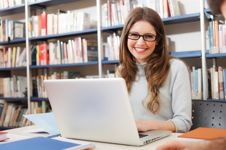 Smiling student using her laptop in a library photo