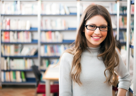college student: Portrait of a beautiful student in a library Stock Photo