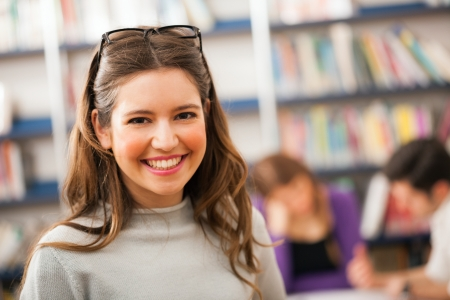 college campus: Portrait of a beautiful student in a library Stock Photo
