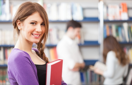 college graduate: Portrait of a beautiful student in a library Stock Photo