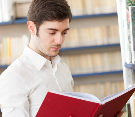 college boy: Guy reading a book in a library