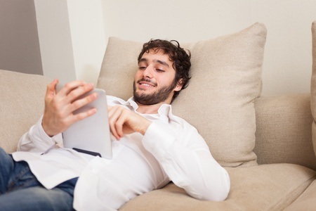 Portrait of a young man using a tablet while relaxing on a couch Stock Photo - 19568061