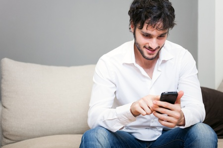Man using a cell phone while sitting on a couch photo