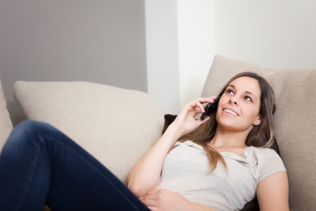 Woman using a cell phone while relaxing on a couch Stock Photo - 19567796