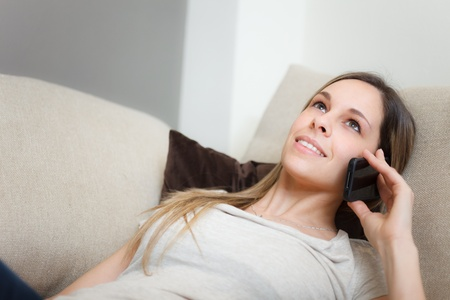 Woman using a cell phone while relaxing on a couch Stock Photo - 19567615