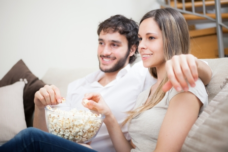 Young couple eating popcorn while watching a movie Stock Photo - 19567973