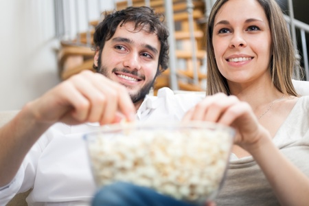 Young couple eating popcorn while watching a movie photo