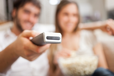 Couple using a remote control while sitting on the couch photo