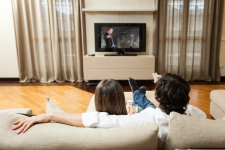 Young couple eating popcorn while watching a movie Stock Photo - 19568070