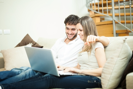 Couple using a notebook while relaxing on the couch Stock Photo - 19567990