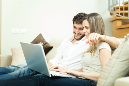 Couple using a notebook while relaxing on the couch Stock Photo - 19567951