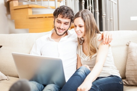 Couple using a notebook while relaxing on the couch photo