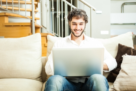 Man using a laptop while sitting on the couch Stock Photo - 19568073