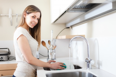 Woman doing dishes in her kitchen Stock Photo