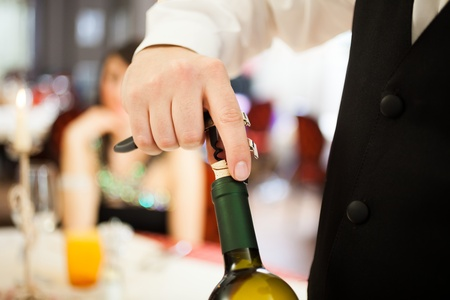 Waiter uncorking a wine bottle in a restaurant photo