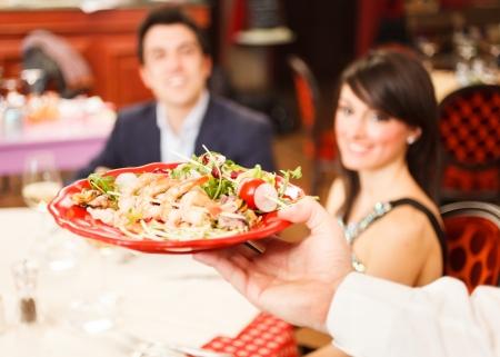 meseros: Camarero que sirve comida de mar a una pareja Foto de archivo