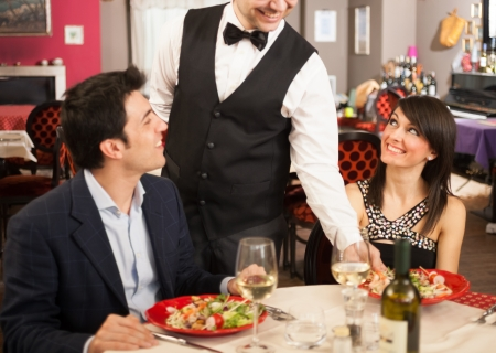 sea food: Waiter serving sea food to a couple