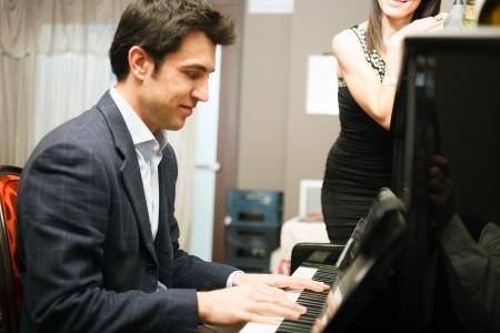 tocando piano: Hombre tocando el piano para su novia Foto de archivo