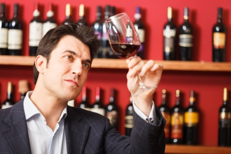 wine tasting: Man tasting a glass of red wine