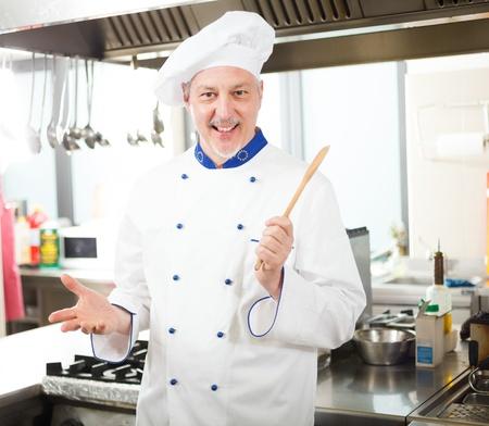 Friendly chef working in his kitchen photo