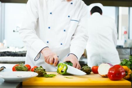 keuken restaurant: Vriendelijke kok voorbereiding van groenten in zijn keuken
