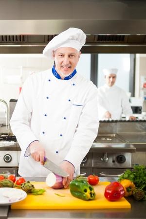 Friendly chef preparing vegetables in his kitchen photo
