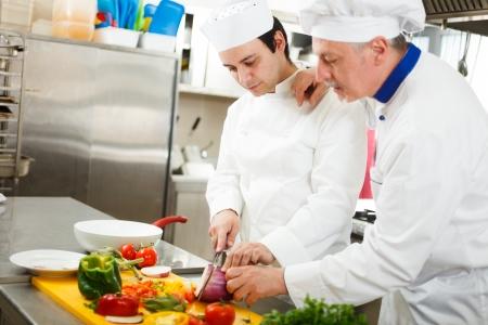 chef italiano: Friendly chef preparando las verduras en su cocina Foto de archivo