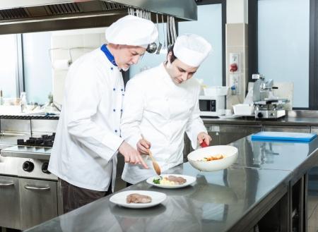 vegetable cook: Capo chef e il suo assistente guarnire un piatto