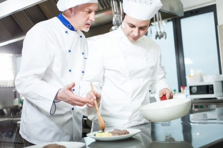 garnishing: Chief chef and his assistant garnishing a dish