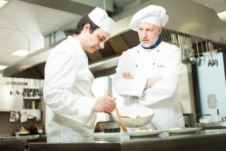 vegetable cook: Capo cuoco guardando il suo assistente guarnire un piatto