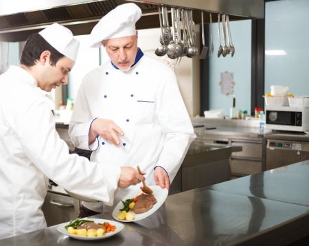 Chief chef watching his assistant garnishing a dish Stock Photo