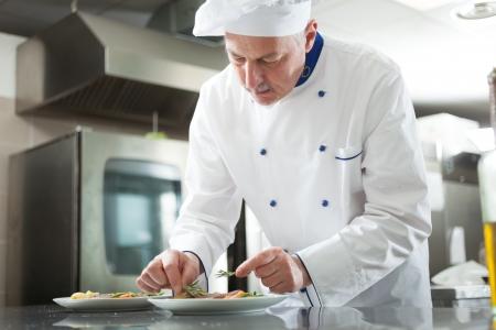 chef cocinando: Cocinero profesional adornar un plato Foto de archivo
