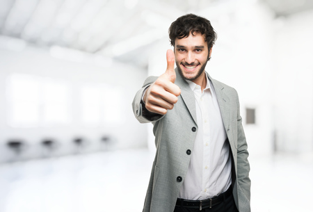 Young man doing thumbs up sign Stock Photo
