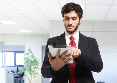 touch technology: Portrait of a young business man holding his tablet Stock Photo