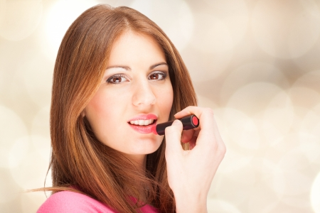 Portrait of a beautiful woman applying lipstick photo