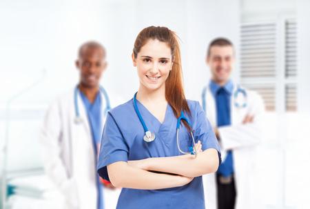 doctoring: Giovane infermiera sorridente davanti alla sua equipe medica