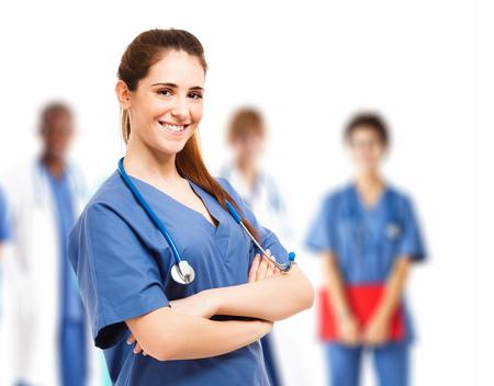 enfermeros: Retrato de una enfermera joven y sonriente en frente de su equipo