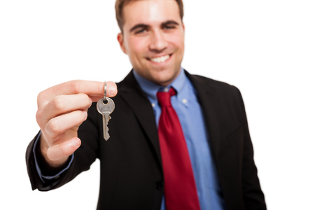 keys isolated: Smiling businessman giving keys to you. Isolated on white Stock Photo