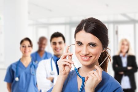 Portret van een lachende verpleegster in de voorkant van een medisch team