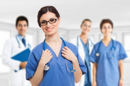 Portrait of a smiling nurse in front of her medical team Stock Photo