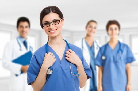 Portret van een lachende verpleegster in de voorkant van haar medische team