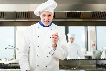 Friendly chef holding a red tomato photo