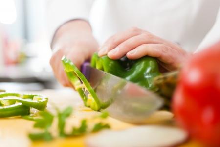 keuken restaurant: Chef-kok voorbereiding van groenten in zijn keuken