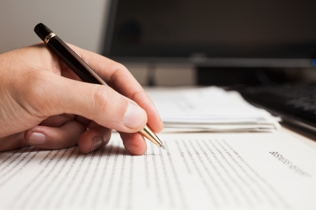 student writing: Man checking text on a document