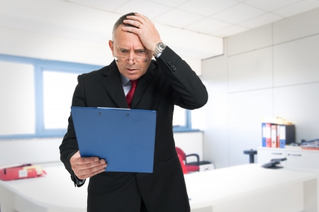angry people: Shocked businessman reading a document Stock Photo