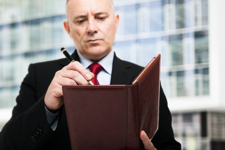 event organizer: Mature businessman writing on his agenda Stock Photo